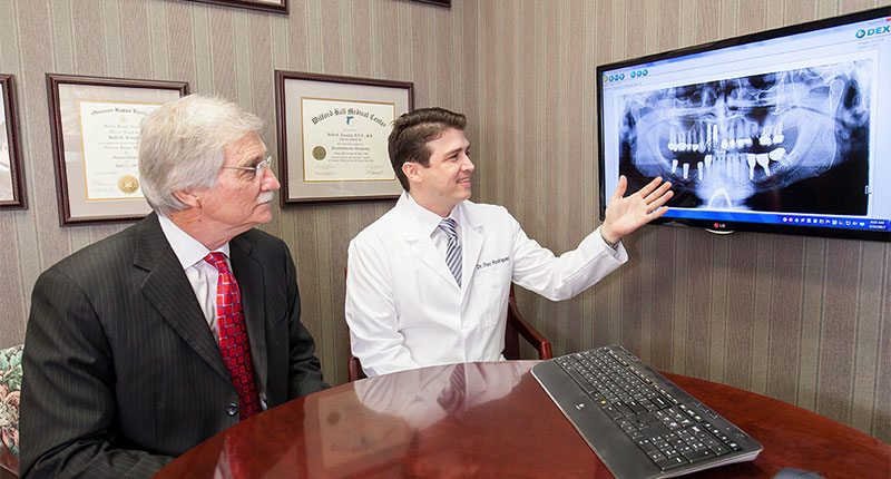 Doctor showing patient X-rays on screen