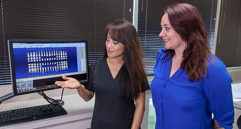 Staff showing patient chart of teeth on screen