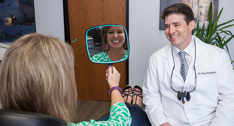 Patient looking at her new beautiful smile in a mirror