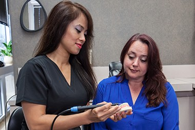 Hygienist showing patient ultrasonic scaler
